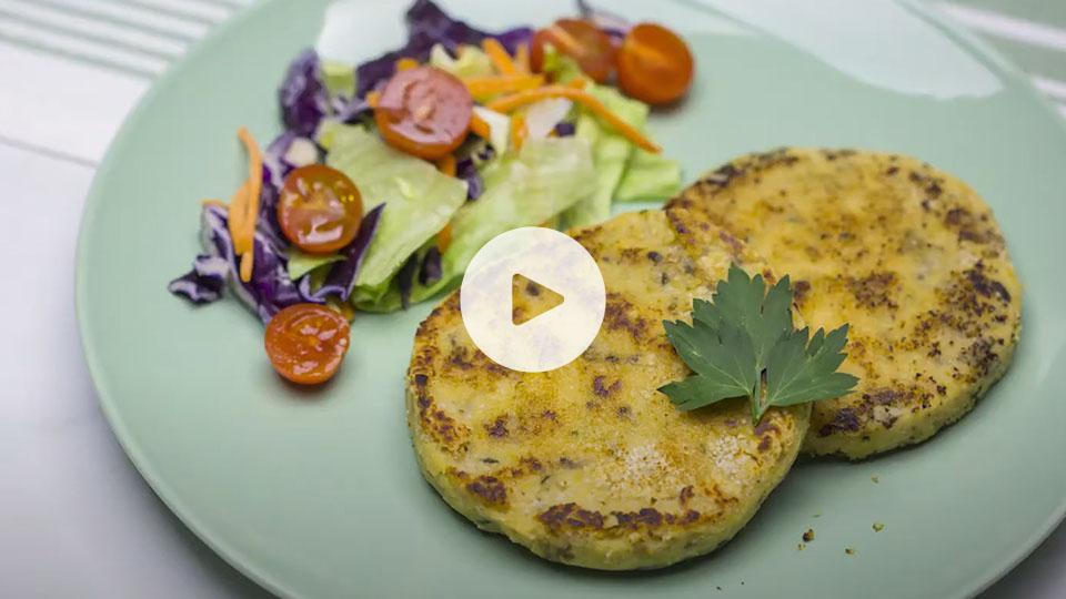 Primer plano de dos hamgurguesas de vegetales alteza emplatadas con ensalada