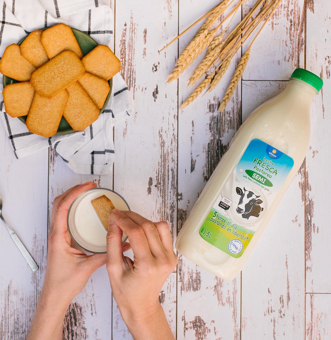 Vista cenital de una botella de leche de pastoreo Alteza, un plato con galletas y unas manos con un vaso de leche