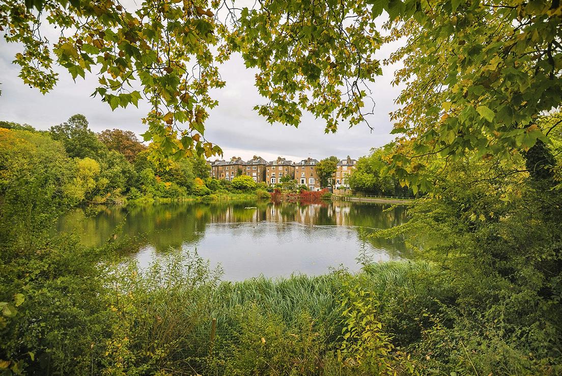 Plano general de un lago y unas casas de estilo inglés al fondo