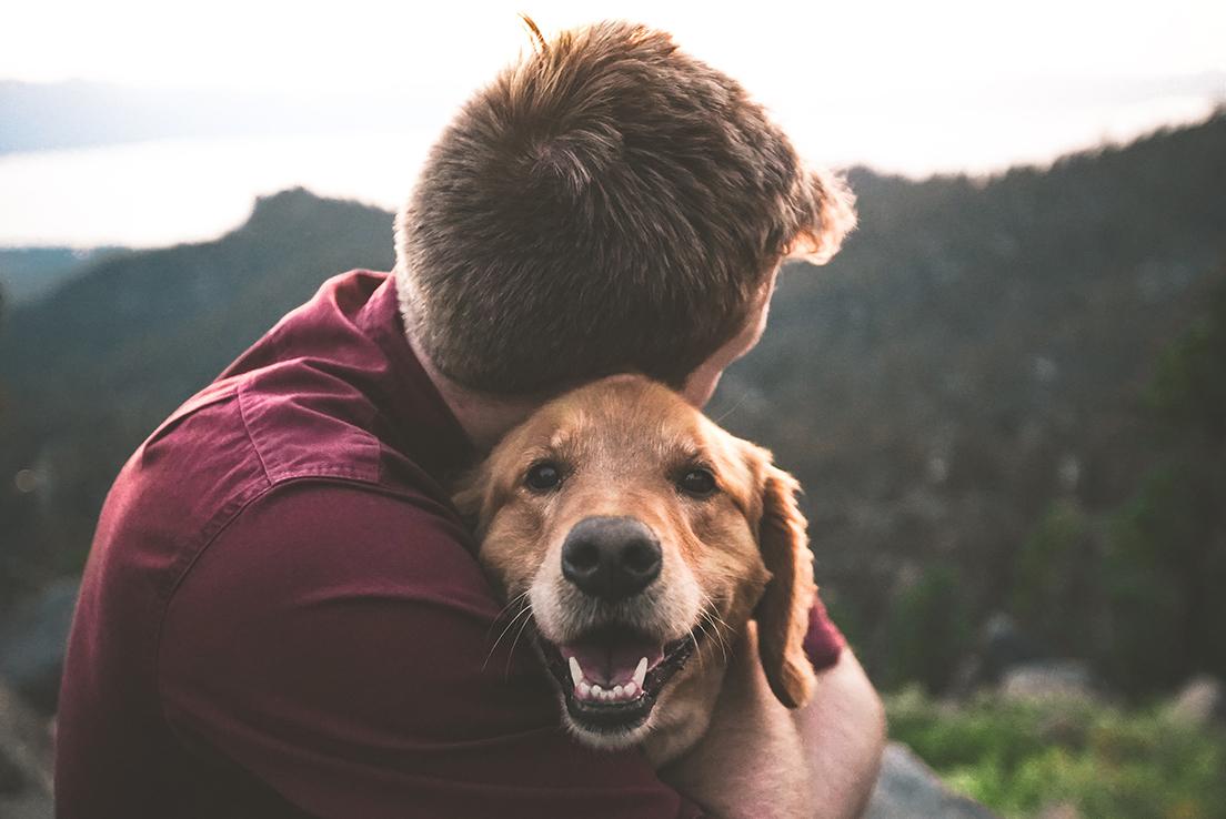Imagen de un hombre abrazando a un perro