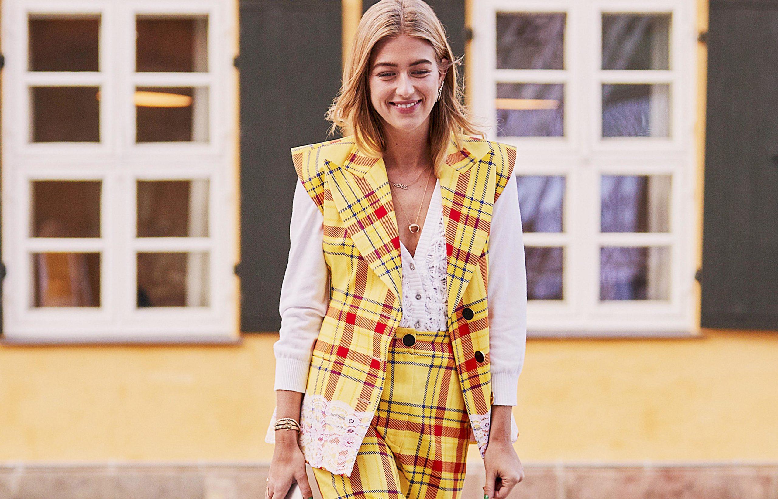 Imagen de una mujer joven, en la calle, vestida con un traje pantalón de cuadros
