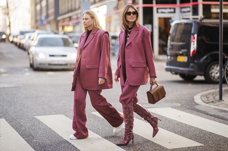 Imagen de dos mujeres vestidas de morado cruzando un paso de cebra