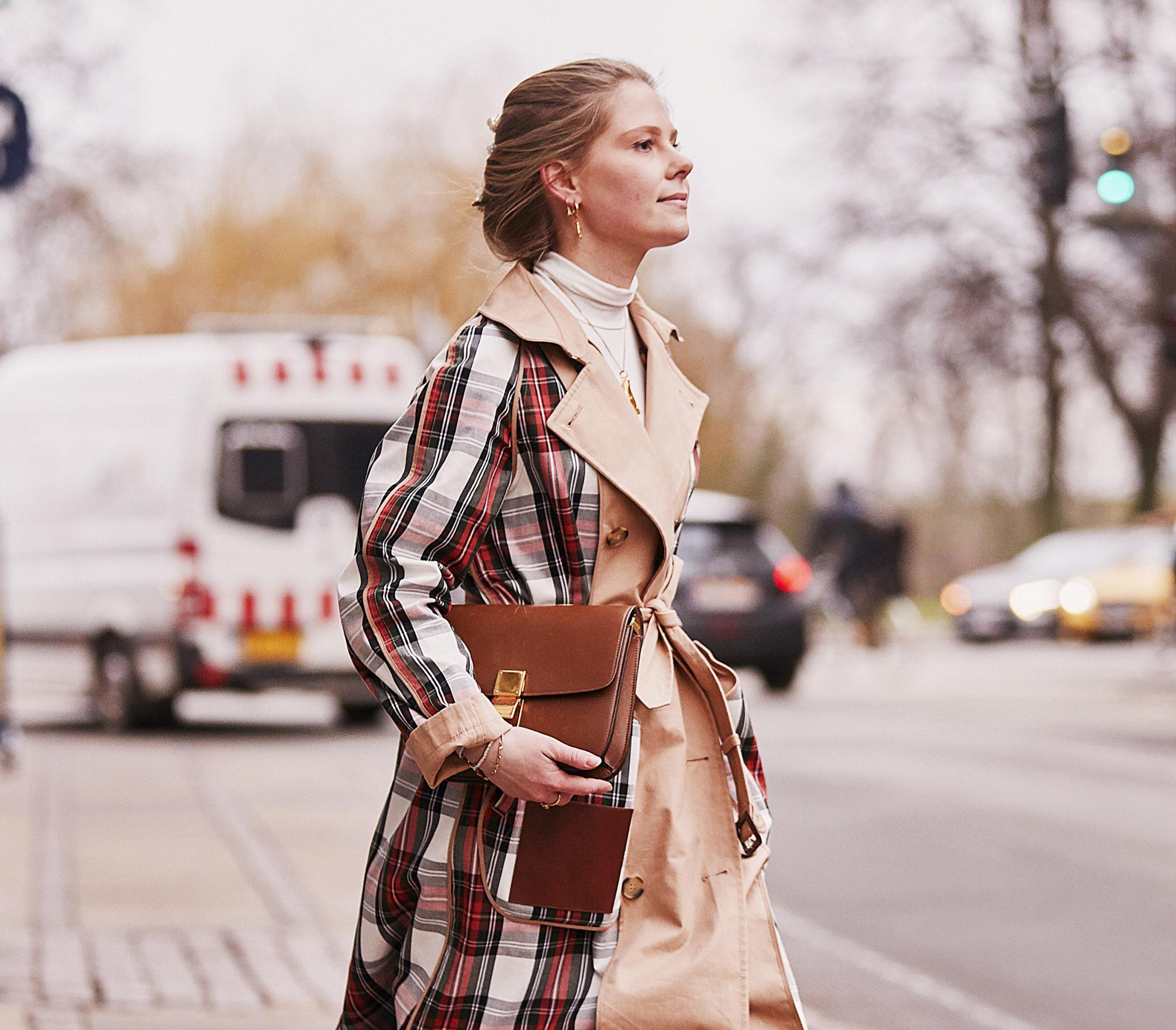 Imagen de una mujer caminado por la calle vestida con un abrigo de cuadros