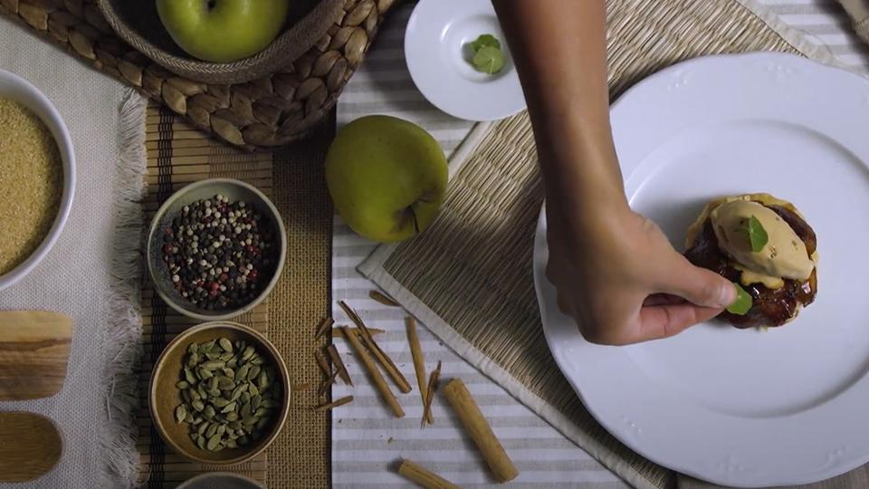 Vista cenital de un bodegón donde se ve una mano decorando un pedazo de pastel de manzana Masalac on turrón de Jijona Alteza