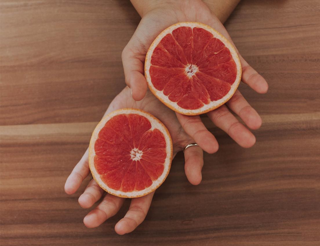 Vista de unas manos de mujer que sostienen un pomelo abierto en dos mitades