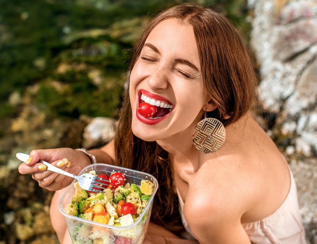 Plano picado de una mujer joven comiendo una ensalada con tomatitos cherry al aire libre
