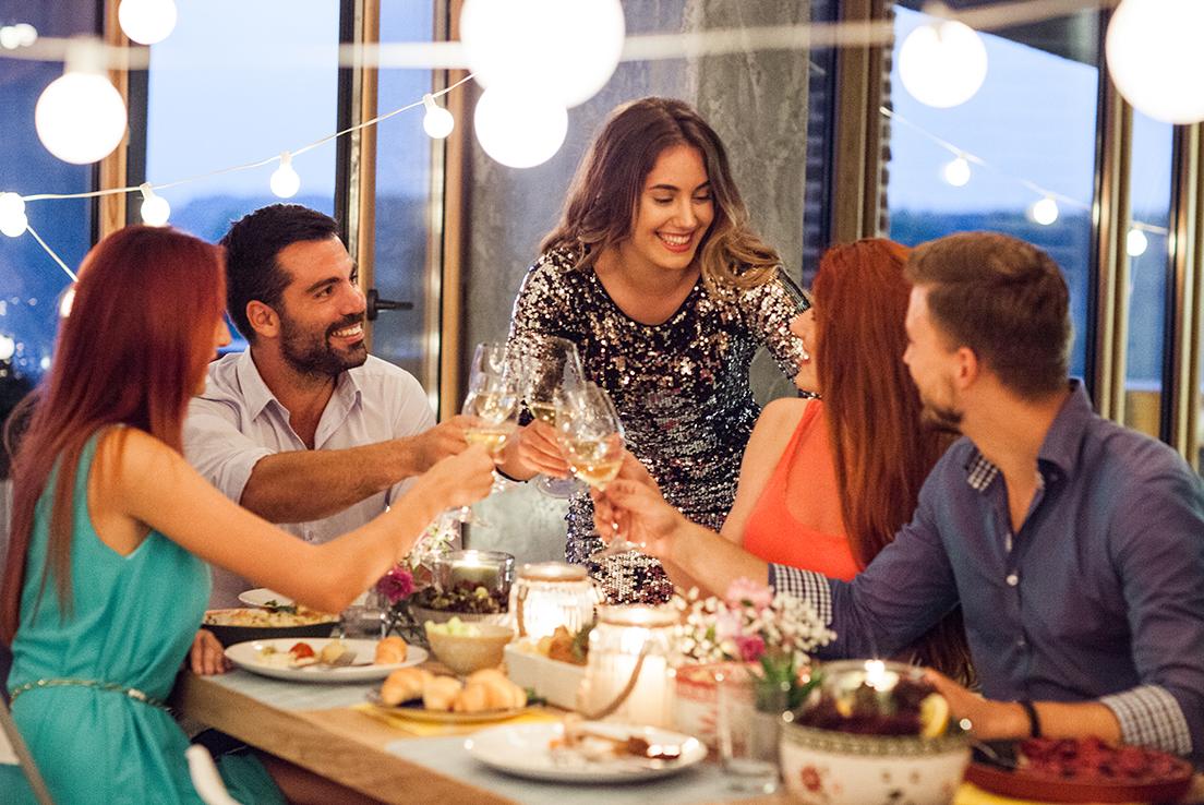 Grupo de hombres y mujeres brindando en una mesa con copas de vino blanco