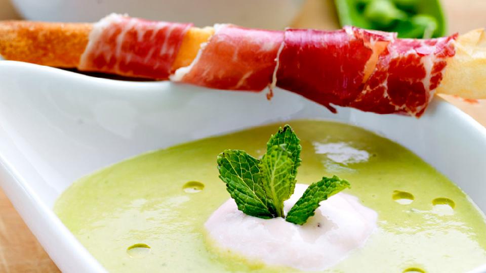 Primer plano de un plato hondo con la receta Alteza de crema fría de guisantes y jamón
