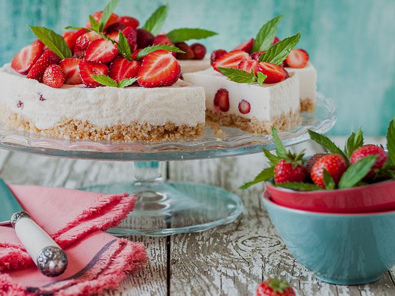 Vista de un bodegón con una tarta de queso y fresas
