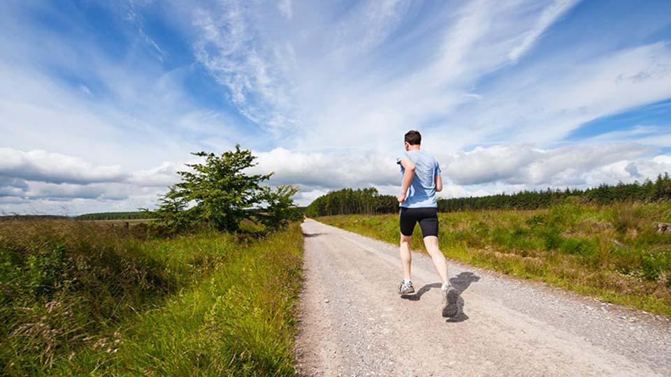 imagen de un chico haciendo running en campo con cielo azul con nubes