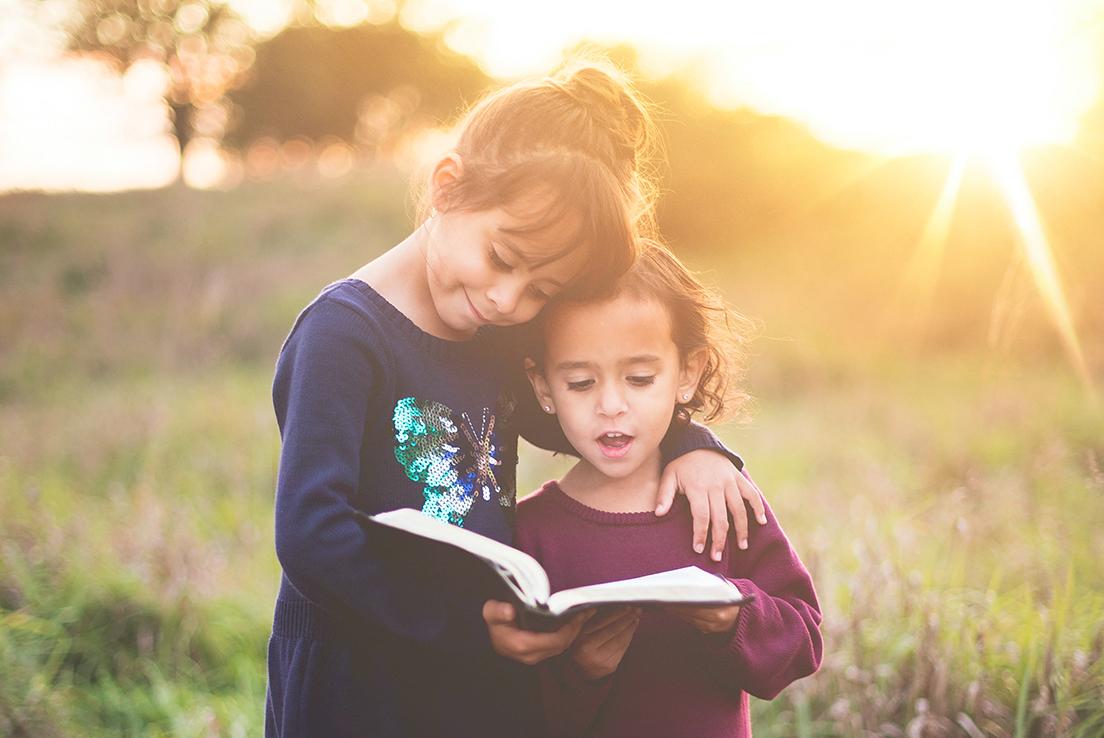 imagen de dos niñas leyendo un libro juntas en el campo