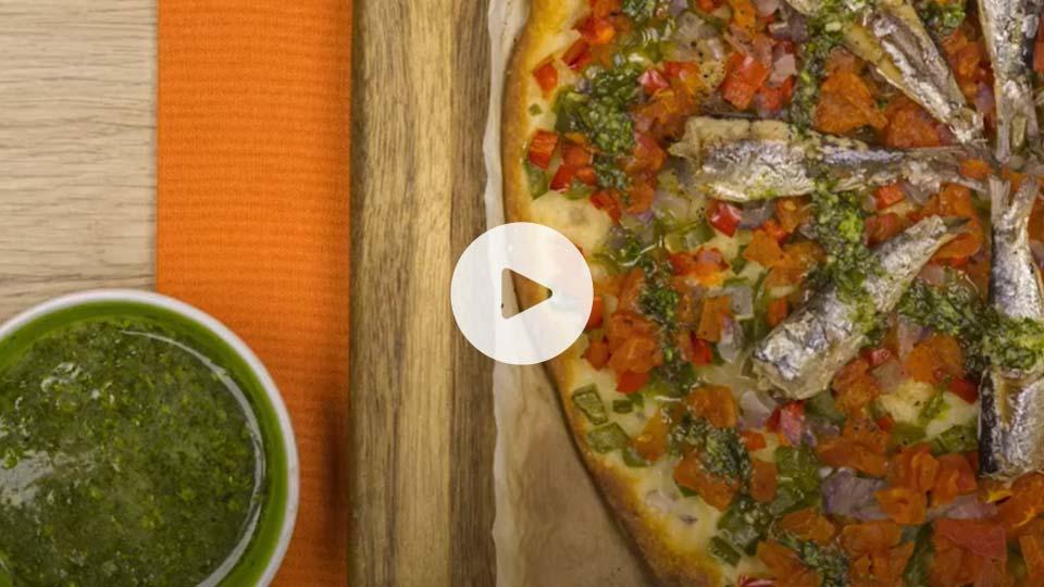 imagen de una coca de verduras con sardinas sobre base de madera y salsa de pesto