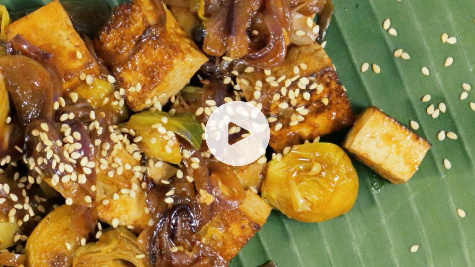 imagen de plato verde con tofu ahumado, alcachofas y coles de bruselas