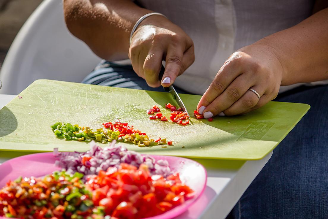 Imagen de persona picando con un cuchillo diferentes verduras sobre tabla de cortar.
