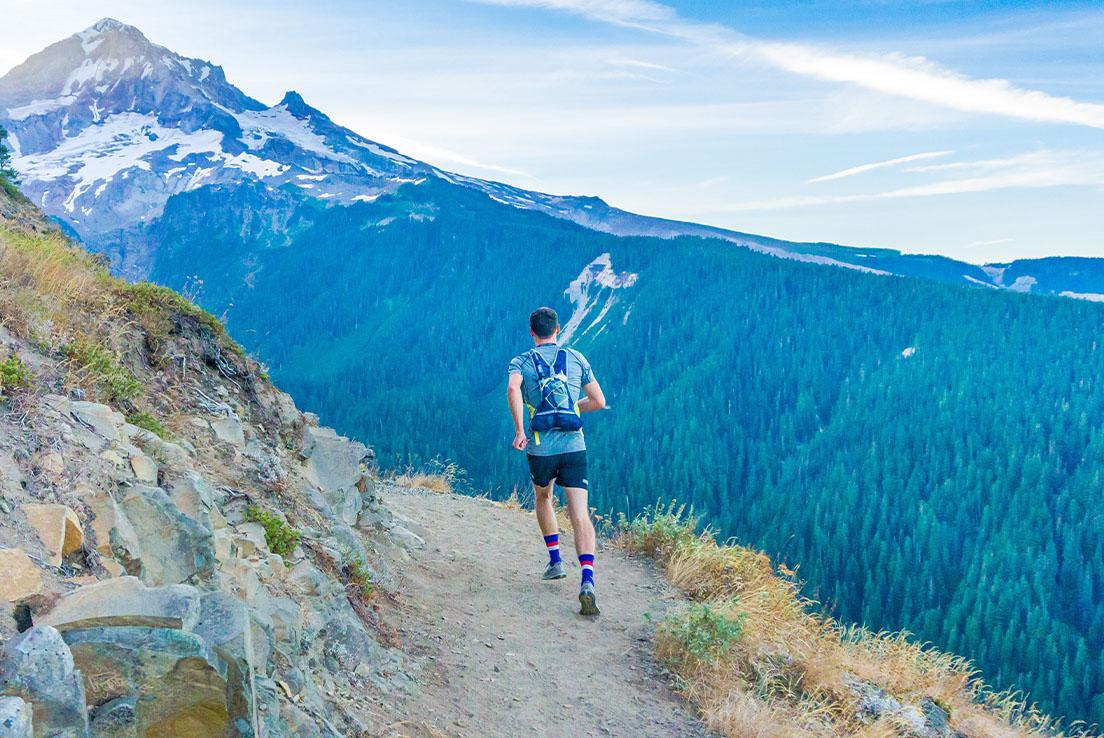 Hombre corriendo por la senda con una vista de una montaña